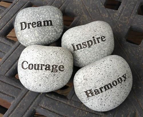 """Tafel met daarop vier stenen. Op elke steen staat een tekst. De teksten zijn: """"Dream, Inspire, Courage, Harmony""""."""
