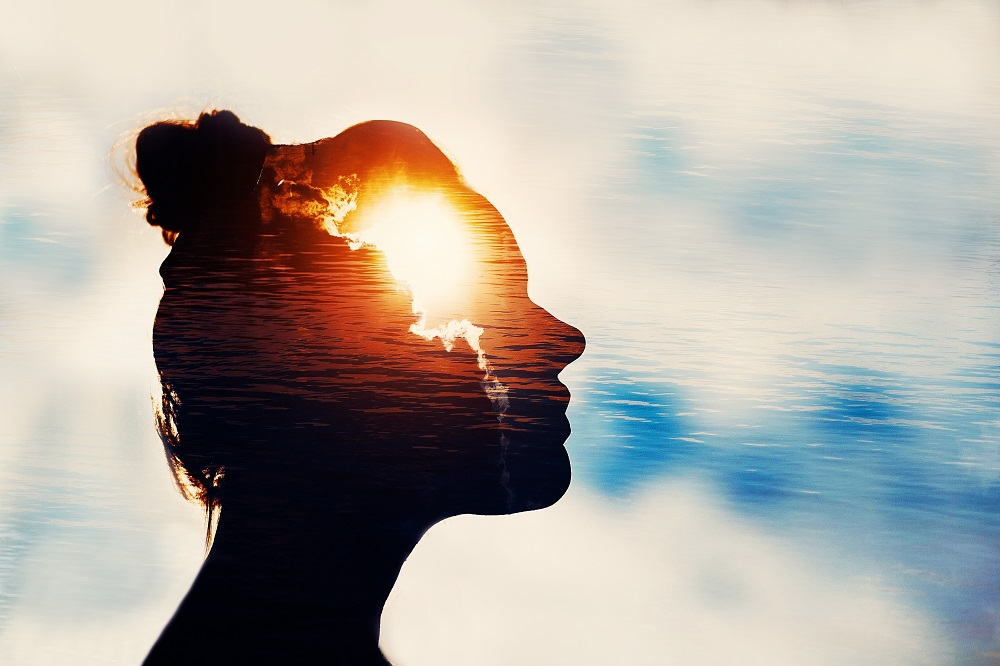 Een foto van water waarin je de lucht ziet weerkaatsen. Een schaduw van een vrouwengezicht waarin je de zon ziet opkomen.