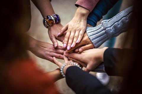 Een foto van 9 personen die gezamenlijk de handen op elkaar leggen.